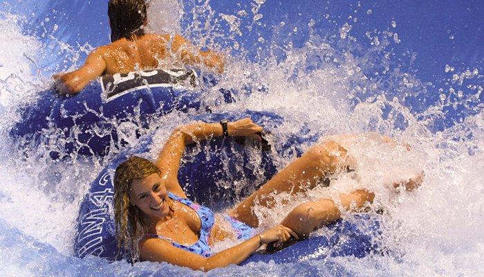 Giovani sorridenti sui gommoni blu dell'Aquafan Riccione tra ondate d'acqua improvvise