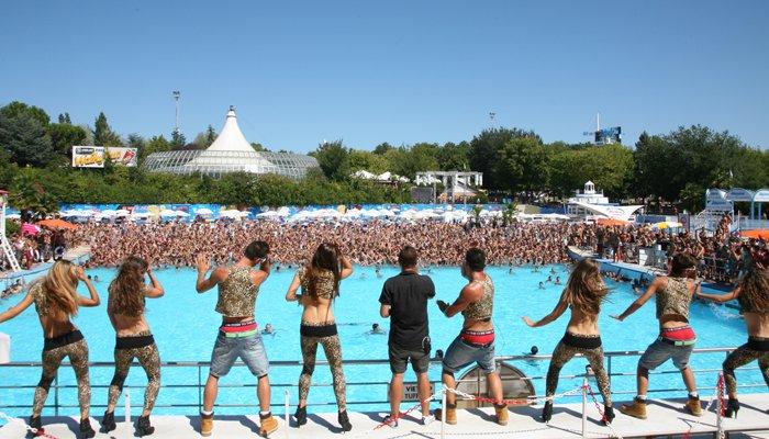 Distesa di giovani ragazzi seguono lo staff di animazione del parco ballando nella piscina con le onde dell'Aquafan Riccione