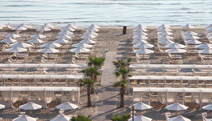 Spiaggia Riccione: stabilimento balneare con ombrelloni bianchi e tende